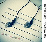 Small photo of a pair of earphones placed on a staff drawn on a notepad simulating musical notes, and the text world music day