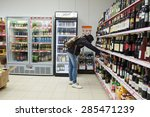 Small photo of MOSCOW, RUSSIA - APRIL 07, 2015: Woman choosing a bottle of wine in supermarket store Pyaterochka. Supermarket Pyaterochka with the most affordable prices. Russia's largest retailer.