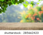 Stock photo empty table covered with sackcloth over blurred trees with bokeh background product display 285662423