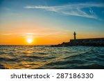 Lighthouse Under Sunburst