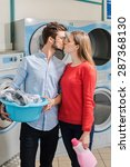 Small photo of Young couple kissing in a launderette, holding a laundry basket