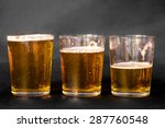 Small photo of Three glasses of beer, one full, one half full and one empty