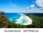 Horizontal view looking onto Tallow Beach in Byron Bay. The Pacific Ocean is a blue turquoise with white waves. The sand is golden, and the beach is surrounded by the green of Arakwai National Park.