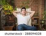 Small photo of Handsome young man in balcony day-dreaming, sitting on chair wearing a v-neck white T-shirt while, in summer