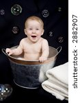 Beautiful one year old baby girl playing with bubbles in a tub - stock photo