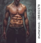 Small photo of Man with great body atomy posing in studio. Grey background