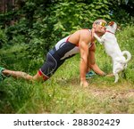 Stock photo fitness man in sportswear with his dog in the forest 288302429