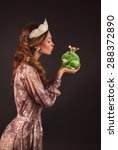 Small photo of blond princess girl kissing a frog green toad like a story tale on white