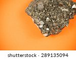 Small photo of Picture of a cut piece of black lead ore with irregular texture, shot on orange paper background with soft shadows, symbolizing playful approach to mining and natural resources industries