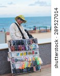 Small photo of VUNG TAU, VIETNAM - JUNE 10, 2015: An unidentified local man pedlar selling sunglasses at the beach looks into camera smiling. Vung Tau is a sea resort in the southern Vietnam.