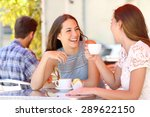 Two friends or sisters talking taking a conversation in a coffee shop terrace looking each other