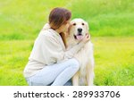 Stock photo owner and happy golden retriever dog together on the grass in sunny summer day 289933706