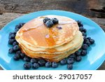 Blueberry pancakes with fresh blueberries and syrup on a matching blue plate. - stock photo