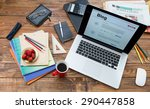 Vacation entertainment concept.  Handcrafted countryside style wooden desk items in creative disorder laptop computer internet page on screen color pencils booklets plate strawberry coffee mug