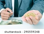 Small photo of closeup of a young caucasian businessman with a pile of buckwheat seeds in his hand and a pile of dollar banknotes on his office desk, depicting the agribusiness concept