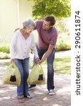 Man Helping Senior Woman With...