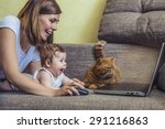 Stock photo the woman with a baby and a cat at the laptop lying on the couch 291216863