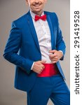 Small photo of Close-up of a handsome nifty man in bright cyan suit and red bow-tie.