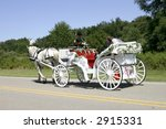 Newly-wed couple in a white, horse-drawn, open carriage - stock photo