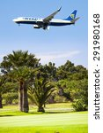 "Small photo of MALAGA, SPAIN - JUNE 23: Ryan Air plane approaching to landing track at AGP Airport, flying over golf course, on June 23, 2015. AGP Airport is close to golf course ""Parador de Malaga""."