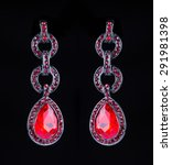 Small photo of earring with colorful red gems on black background