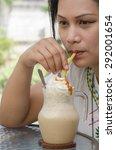 the girl eats a caramel latte. | Shutterstock . vector #292001654