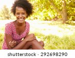 young woman sitting on grass... | Shutterstock . vector #292698290