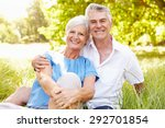 senior couple sitting on grass... | Shutterstock . vector #292701854