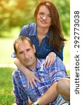 Small photo of Portrait of happy, caucasian couple in a summer park. Shallow doff, lens flare