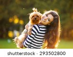 Stock photo beautiful girl in a striped sweater smiles and holds a small dog 293502800