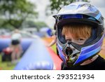 Young boy wearing a motorcycle helmet. Young boy wearing motorcycle helmet, at a county fairground, waiting to go on a quad bike. Safety concept - stock photo