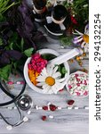 Small photo of Alternative medicine herbs, berries and stethoscope on wooden table background