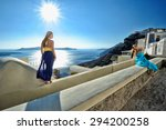 Two young women take a photo of each other in the town of Fira, Santorini island, Greece