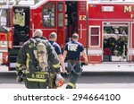 Small photo of MOORHEAD, MN/USA - MAY 2, 2015: Fiire alarm at apartment complex goes off and the Moorhead Fire Department are on the scene. Firefighters carry gear back to the fire truck after giving the all clear.