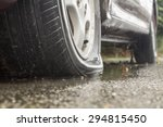 Car flat tire in rainy day - stock photo