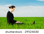 smiley businesswoman resting with laptop at the green meadow - stock photo