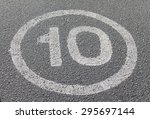 Small photo of Ten Miles per hour painted road sign on asphalt