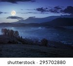 village behind the agricultural meadow with yellow trees on hillside in autumn mountains at night in full moon light - stock photo