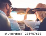 Enjoying road trip together. Rear view of joyful young couple having fun while riding in their convertible  - stock photo