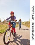 Little girl and mother riding on bicycles - stock photo