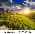 huge boulders on the top edge of hillside with grass and dandelions in high mountains under the rainbow in evening light - stock photo