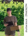 Small photo of Smiling attractive female courier in a cap delivering a parcel to the door of a house holding out a clipboard for signature to acknowledge receipt, against a background of fresh garden leaves