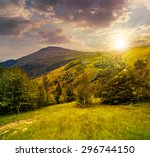 composite image of path through the green forest to peak on slope of mountain range in evening light - stock photo