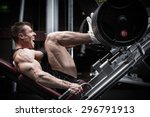Small photo of Man in gym training at leg press to define his upper leg muscles