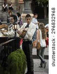 Small photo of GUANAJUATO, MEXICO - JUNE 30, 2015: Handsome street performer dressed in traditional attire is playing a Mexican Vihuela five string guitar. Mariachi is a form of folk music from Mexico.