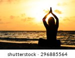 woman meditation on sunset beach | Shutterstock . vector #296885564