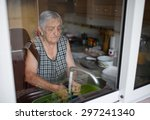 elderly woman washing dishes in ... | Shutterstock . vector #297241340