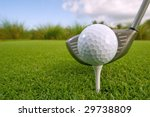golf ball and driver on lush tropical course with copy space - stock photo