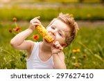 young boy eating an ear of... | Shutterstock . vector #297627410