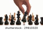 Chess board and hand picking up the queen on a white background - stock photo
